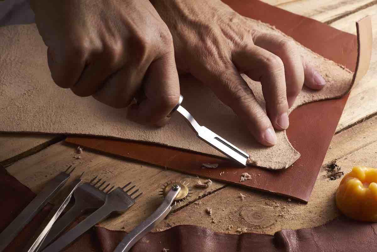 Man Shaving Leather on Wood Table