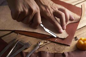 Man Shaving Leather on Wood Table